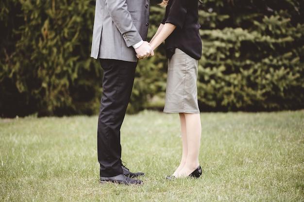 Paar dat formele kleding draagt en de handen van elkaar houdt