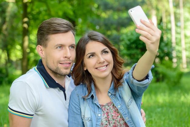 Paar dat foto op slimme telefoon op romantische picknickdatum neemt.