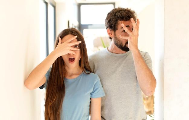 Paar dat geschokt, bang of doodsbang kijkt, gezicht bedekt met hand en tussen vingers gluurt