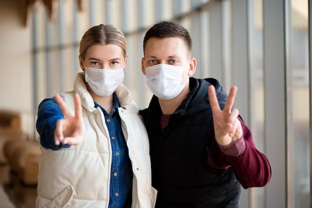 Paar dat gezichtsmasker draagt tijdens coronavirus op luchthaven