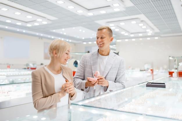 Paar dat gouden decoratie in juwelenwinkel koopt