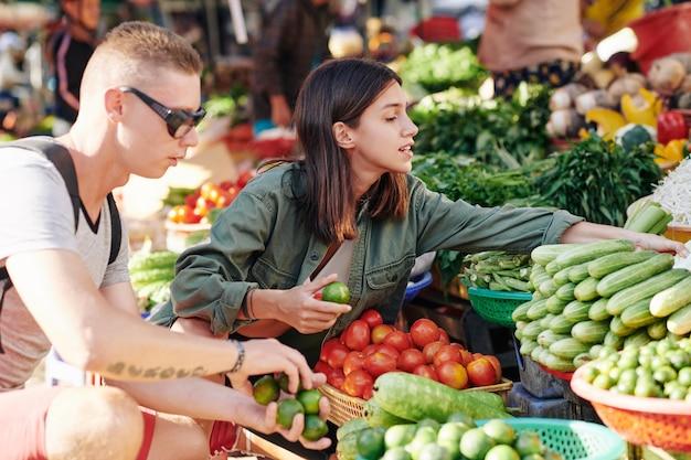 Paar dat groenten kiest bij markt