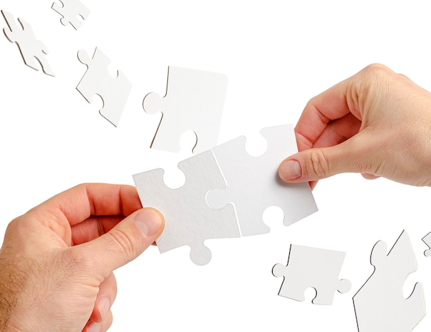 Paar dat handen puzzel houdt die op wit wordt geïsoleerd. teamwork en zakelijke samenwerking concept.