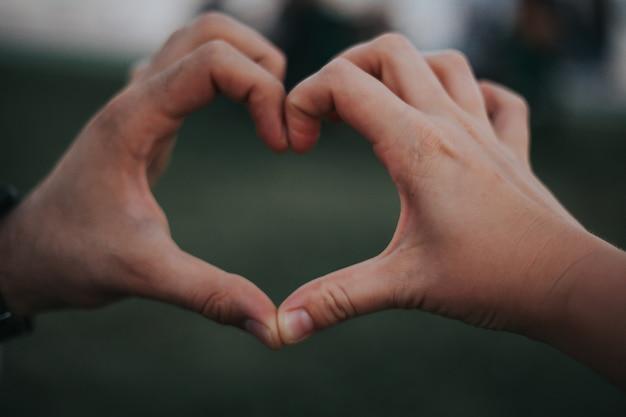 Paar dat hart met hun handen met groene achtergrond maakt. hou van concept. hart concept maken.