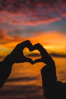Paar dat hart van handen op overzeese kust maakt