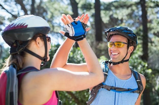 Paar dat helm draagt die hoogte vijf geeft tijdens avontuur