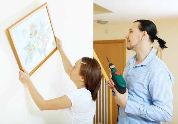 Paar dat het kunstbeeld op de muur hangt