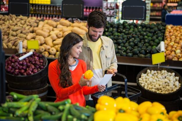 Paar dat hun blocnote controleert terwijl het winkelen in organische sectie
