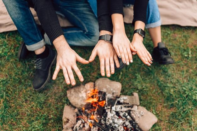 Paar dat hun handen verwarmt boven vreugdevuur