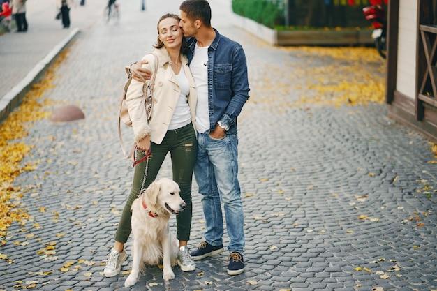 Paar dat hun hond op een zonnige de herfstdag loopt