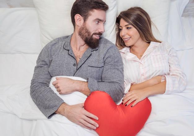 Paar dat in bed met rood stuk speelgoed hart ligt