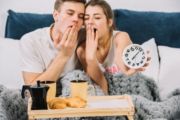 Paar dat in bed met voedseldienblad geeuwt