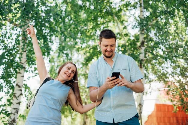 Paar dat in berkbos loopt met hoofdtelefoons
