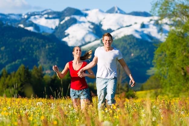 Paar dat in de weide met berg loopt