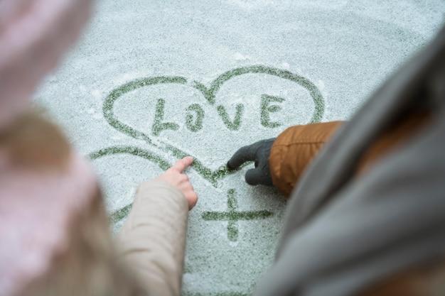 Paar dat in de winter liefde in de sneeuw schrijft