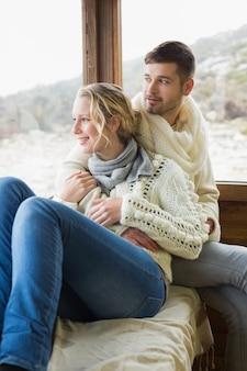 Paar dat in de winterslijtage door cabinevenster kijkt