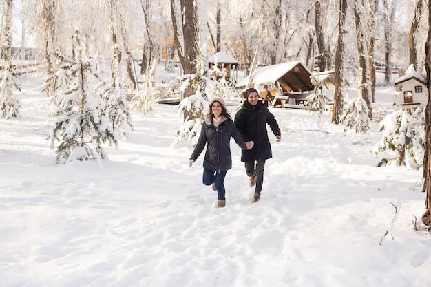 Paar dat in een besneeuwde winterpark loopt