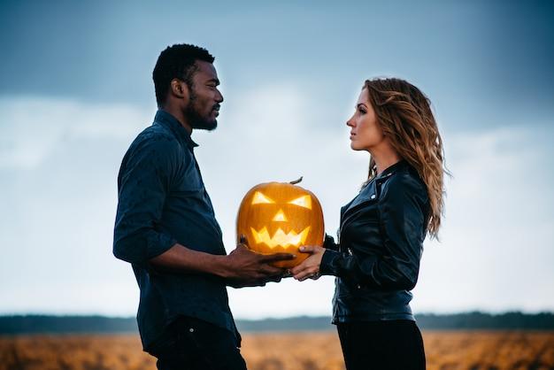 Paar dat in pompoenveld staat en enge gezichtspompoen vasthoudt, concept halloween