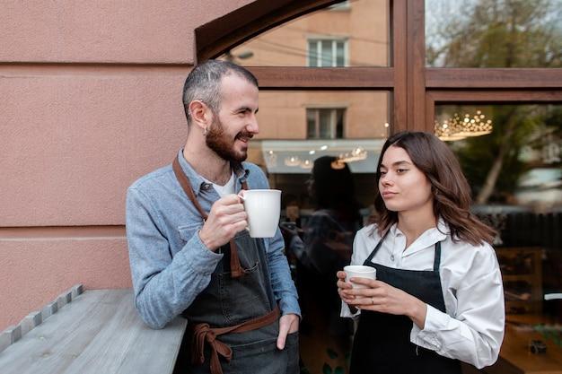 Paar dat in schorten van koffie buiten geniet