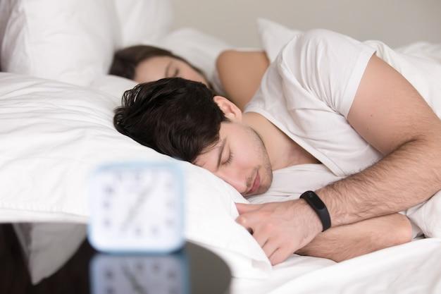 Paar dat in slaap in bed, man ligt die polsband slim horloge draagt