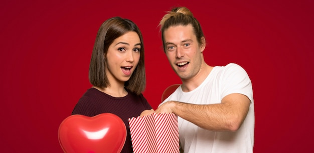 Paar dat in valentijnskaartag popcorns over rode achtergrond eet