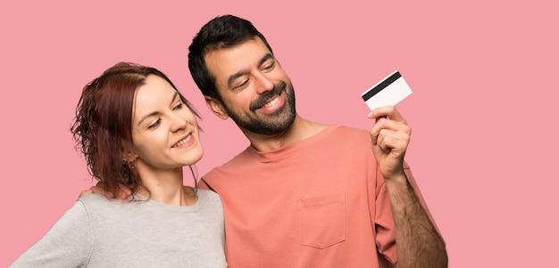 Paar dat in valentijnskaartdag een creditcard houdt en over geïsoleerde roze achtergrond denkt