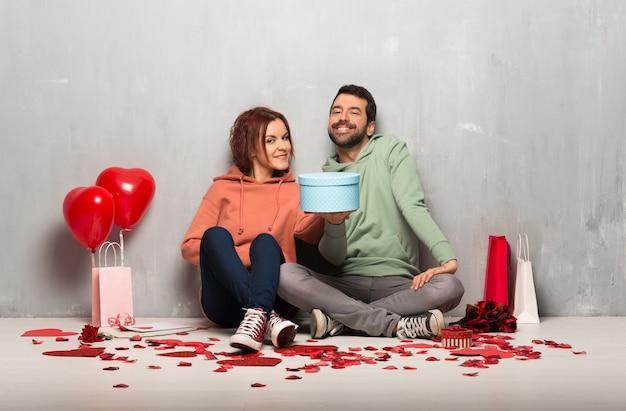 Paar dat in valentijnskaartdag een gift in handen houdt