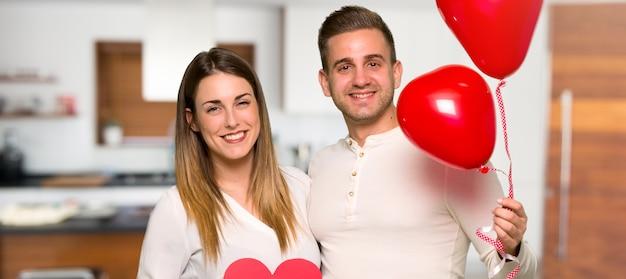 Paar dat in valentijnskaartdag een hartsymbool en ballons in een huis houdt
