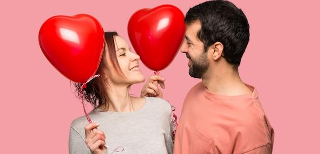 Paar dat in valentijnskaartdag een hartsymbool en ballons over geïsoleerde roze achtergrond houdt