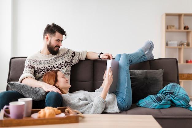 Paar dat in woonkamer een boek bekijkt