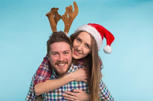Paar dat kerstmiskostuums op blauw draagt