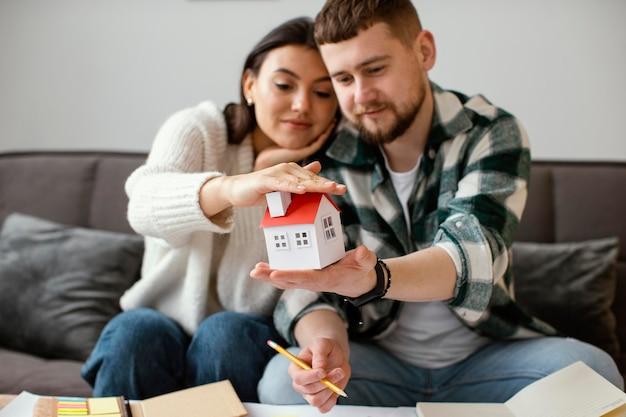 Paar dat klein huis middelgroot schot houdt Gratis Foto