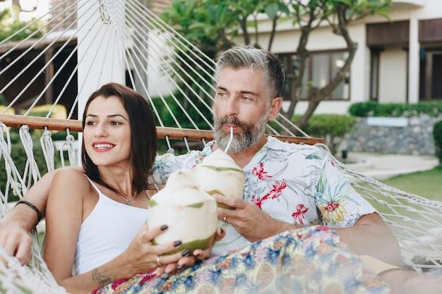 Paar dat kokosnotensap in een hangmat drinkt