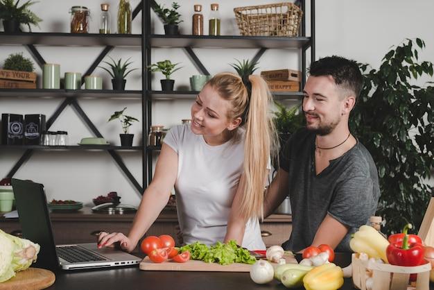 Paar dat laptop bekijkt die zich achter het keukenteller met groenten bevindt