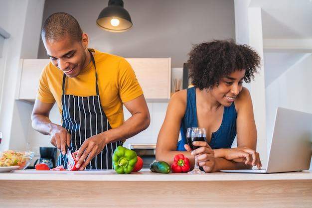 Paar dat laptop met behulp van terwijl het koken in keuken