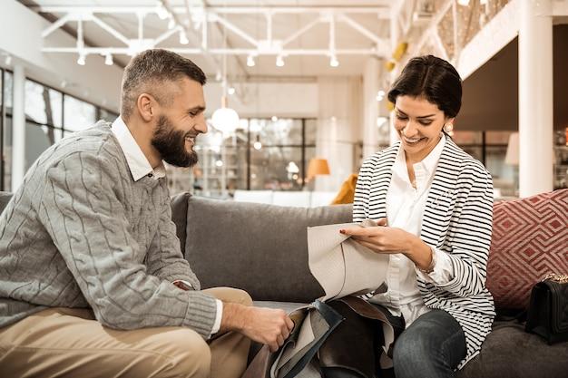 Paar dat materiaal kiest. glimlachende donkerharige vrouw raakt voorbeeld van dik materiaal in haar handen terwijl echtgenoot dichtbij zit
