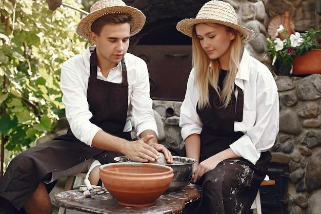 Paar dat met bruine schorten een vaas maakt