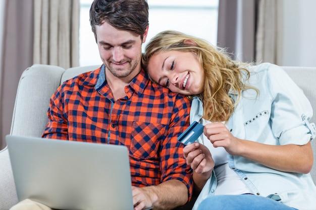 Paar dat met creditcard op laptop in de woonkamer betaalt