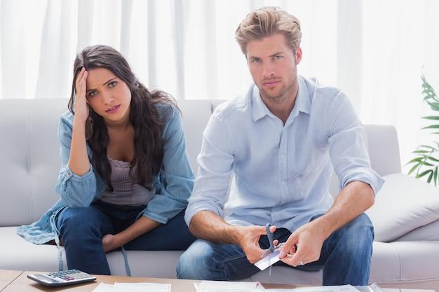 Paar dat ongerust kijkt terwijl het doen van hun rekeningen