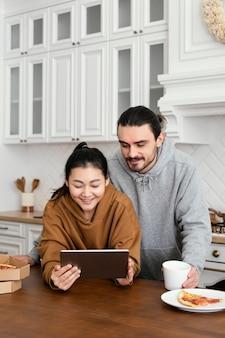 Paar dat ontbijt in de keuken neemt en een tablet gebruikt