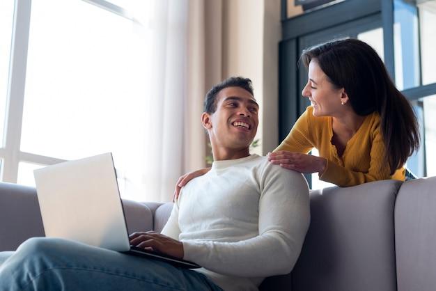 Paar dat op bank bij elkaar glimlacht