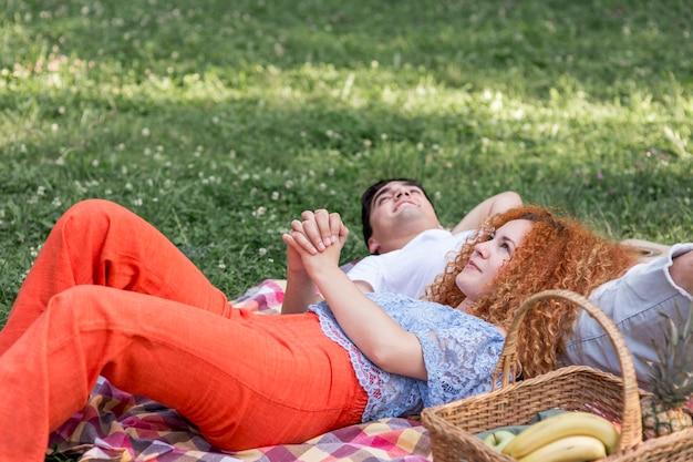 Paar dat op een deken legt en aan de hemel kijkt