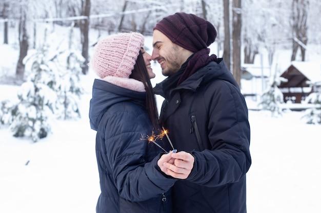 Paar dat op elkaar kijkt en sparkles in park met sneeuw houdt