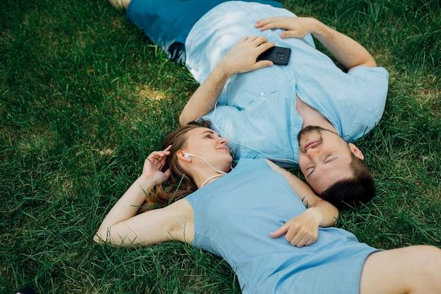 Paar dat op gras met oortelefoons ligt