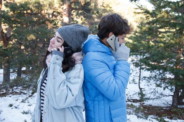 Paar dat op telefoon in het bos op een sneeuwdag spreekt.