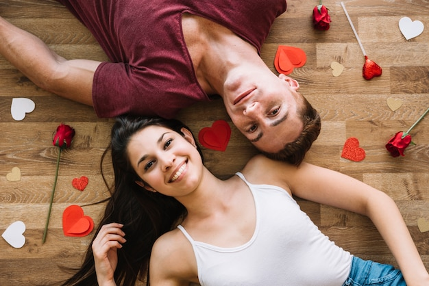 Paar dat op vloer met document harten ligt
