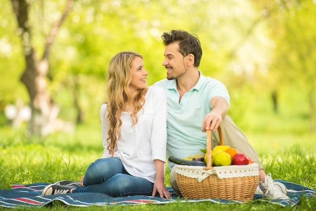 Paar dat picknick op het gazon in de zomerpark heeft.