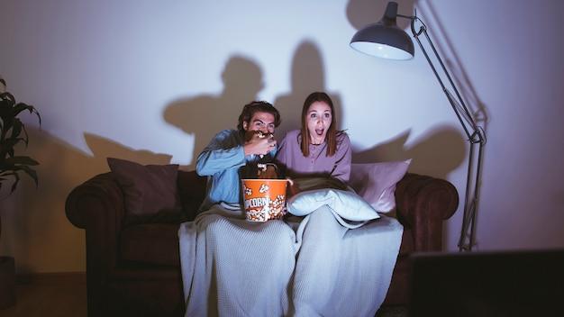 Paar dat popcorn eet en een filmnacht heeft