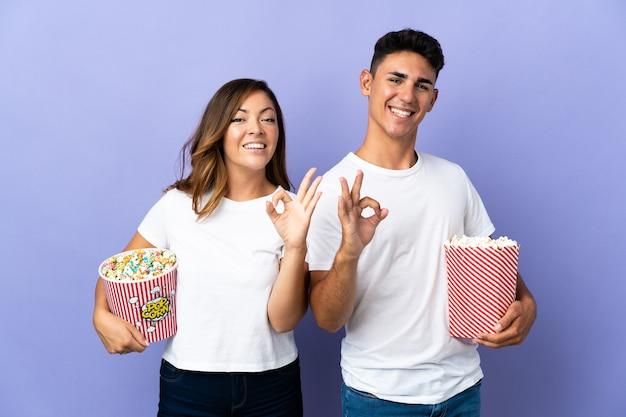 Paar dat popcorn eet tijdens het kijken naar een film op paars met een ok teken met vingers