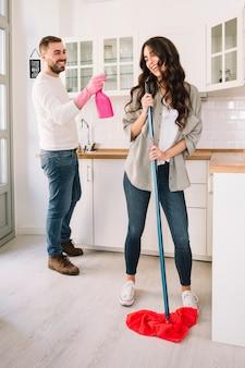 Paar dat pret heeft terwijl het schoonmaken van keuken